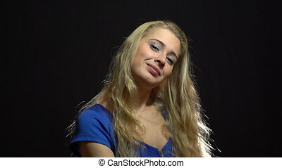 Beautiful Sexy Blonde Girl in Blue Dress is Flirtis and Sending a Fly Kiss in Studio with Black Background.