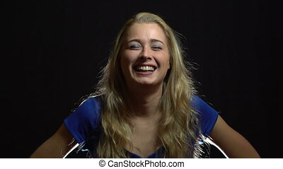 Beautiful Sexy Blonde Girl in Blue Dress Laughting in Studio with Black Background