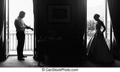 Beautiful sexy bride and handsome groom separate on balcony at resort b&w