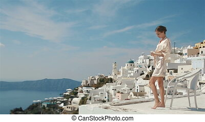 Beautiful sexy brunette bride in robe sitting at roof with her legs crossed and enjoying the view of mountains and sea