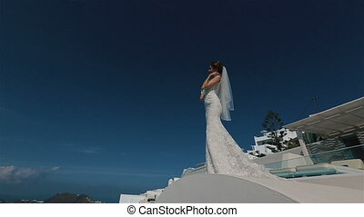 Beautiful sexy brunette bride in wedding dress with bouquet in her hands moves on the roof, Santorini closeup