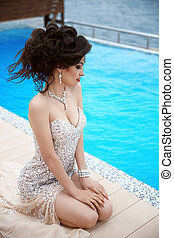 Beautiful sexy brunette elegant model woman in fashion dress with diamonds