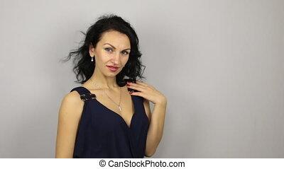 Beautiful sexy brunette flirting and pose, near the gray...