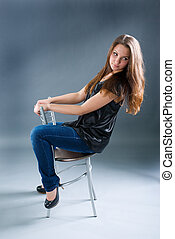 sexy brunette girl sitting on chair