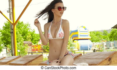 beautiful Sexy brunette in glasses and a bathing suit on a beach straightens hair