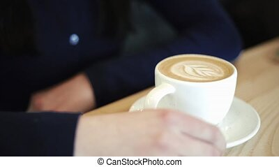 Beautiful sexy brunette sitting in cafe on table talking with a man sitting opposite Coffee close-up