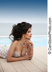 Beautiful sexy brunette woman model in elegant fashion dress with diamond jewelry, makeup red lips, hairstyle. Girl model posing by swimming pool, Resort.
