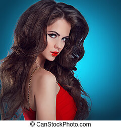 Beautiful sexy brunette woman with long hair. Red lips and dress.