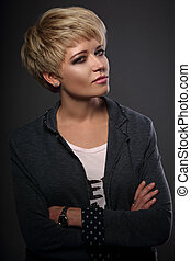 Beautiful sexy business woman with short bob blond hairstyle in fashion jacket on grey background. Closeup portrait