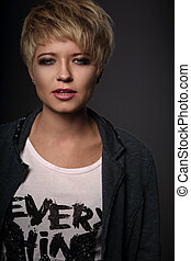 Beautiful sexy cocky woman with short bob blond hairstyle in fashion jacket on grey background. Closeup portrait