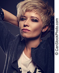 Beautiful sexy cocky woman with short bob blond hairstyle and black smoky eyeshadow makeup in fashion jacket on grey background. Closeup toned portrait