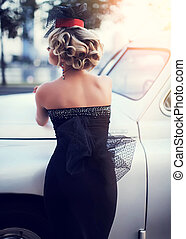 beautiful sexy fashion blond girl model with bright makeup and curly hairstyle in retro style posing near old white car
