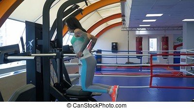 Beautiful sexy female athlete doing push-ups on parallel bars in gym. Athlete woman workout out arms on dips horizontal parallel bars Exercise training triceps and biceps doing push ups. Athlete woman
