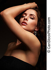 Beautiful sexy female model posing in fashion earrings on black background. Closeup