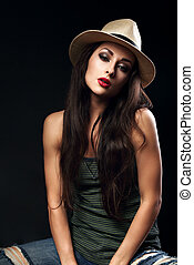 Beautiful sexy female model with long brown hair posing in cowboy summer hat and fashion top and ripped jeans on dark background