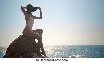 beautiful sexy girl in a hat sits on a stone in a white bathing suit and looks at the sea at the waves