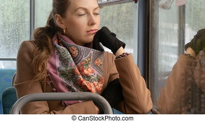 Beautiful sexy girl looking sad at the window of a streetcar.