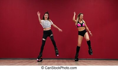 Beautiful sexy girl on a red background with a wall perform fitness exercises on shoes with a spring. Cardio training in the jump style. Jumping without stopping. Burning fat and sternafia figure with boots on the springs. kangoo jumps
