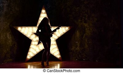 Beautiful sexy girl playing electric guitar in the music hall, slow motion, silhouette