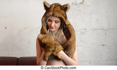 beautiful sexy girl showing a fur hat with funny ears