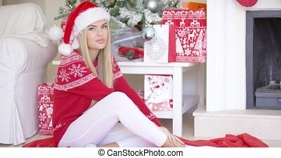 Beautiful sexy girl sitting on the floor next to Christmas tree