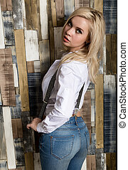 Beautiful sexy girl with big boobs in a vintage blue jeans and white shirt poses near a wooden wall.