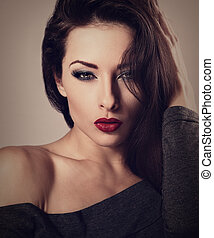 Beautiful sexy makeup woman with red lipstick and long lashes looking hot. Toned vintage closeup portrait