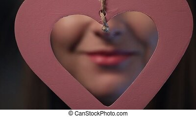 Beautiful sexy pink lips giving kiss through the hearshaped...