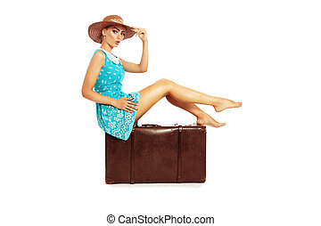 Beautiful sexy tanned barefoot pin-up girl in stylish dress and hat sitting on big vintage bag over white backgroun