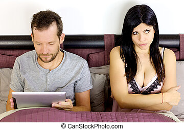 Beautiful sexy woman bored about husband playing with tablet