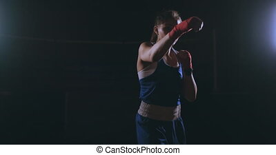 Beautiful sexy woman boxer dynamically strikes directly into...