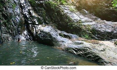 Beautiful sexy woman enjoying bathing near natural waterfall on Koh Samui.