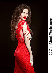 Beautiful sexy woman in red fashion dress isolated on black background. Makeup. Beauty Brunette Girl. Healthy Long Hair. Manicured nails.