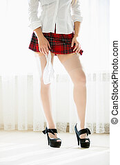 woman in stocking and red school skirt holding panties in...