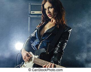 Beautiful sexy woman playing electric guitar