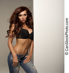 Beautiful sexy woman posing wearing jeans and bra. Long healthy brunette hair.