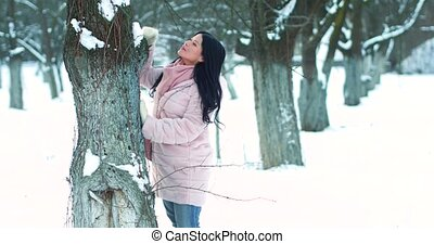 Beautiful sexy woman take care of tree in snowy garden.