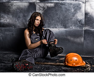 Beautiful sexy worker with a pickaxe and helmet. Seductive and beautiful woman miner sitting on a floor on steel background