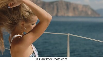 Beautiful sexy young blonde woman on a yacht