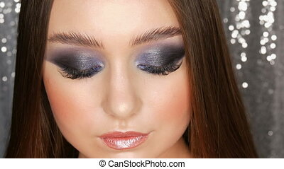 Beautiful sexy young girl with evening blue make-up smoky eyes long hair and cosmetic colored contact lenses posing in the model studio on the silver background