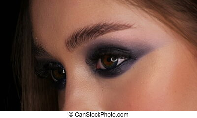 Beautiful sexy young girl with evening blue make-up smoky eyes long hair and cosmetic colored contact lenses posing in the model studio on the black background cloe up face