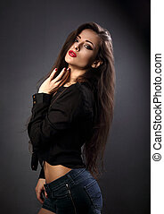 Beautiful sexy young make-up model with red lipstick posing in jeans shorts and black shirt with abdomen on dark shadow black background