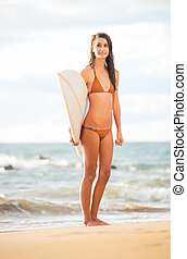 Beautiful sexy young surfer girl in bikini on the beach at sunset