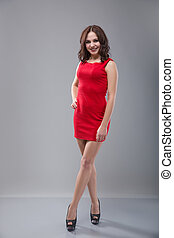 Beautiful sexy young woman in a red dress on a gray background