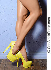 Beautiful shapely female legs in yellow shoes leather reptile