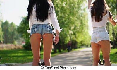 Beautiful shapely legs young girls in short chertah closeup on white gyrometer the electric Segway ride through the Park