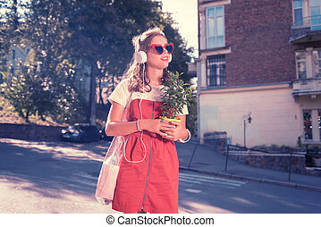 Beautiful shopaholic feeling happy while crossing street with new home plant
