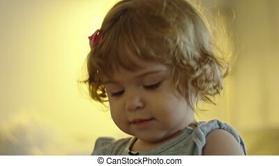 Slow motion close-up shot of a beautiful baby girl hugging and playing with her elephant stuffed animal toy