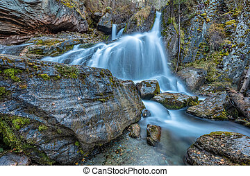 Beautiful shot of waterfall in Altai mountains in Siberia, Russia. Smooth, silky water. Long exposure. Rocks and logs in the foreground.