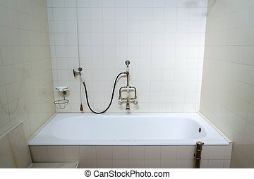 Beautiful shower bath with hot and cold water taps, white tile design wall, modern functionalism architecture